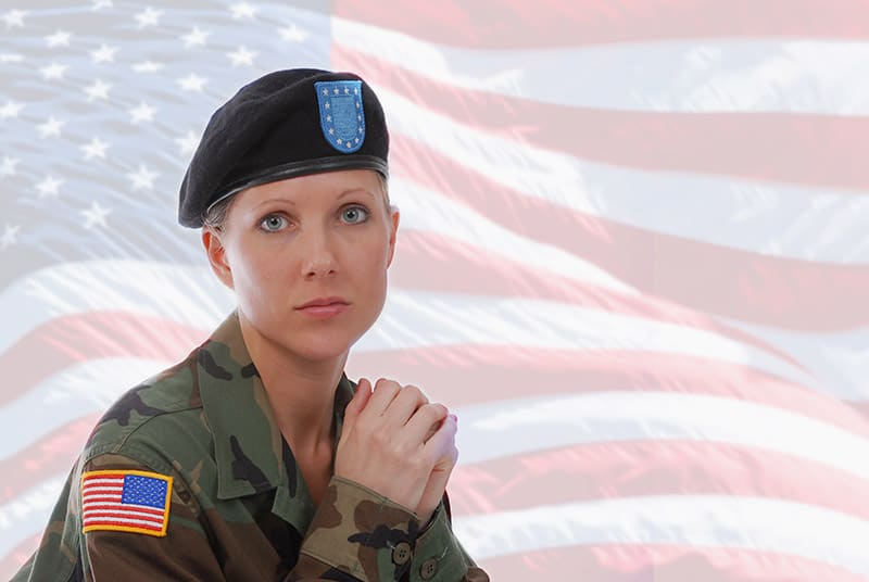 Military woman in a uniform in front of an American Flag