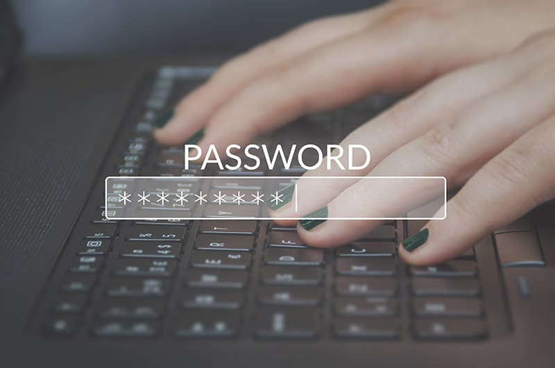 Woman's hands typing on a keyboard with the word password overlaying it